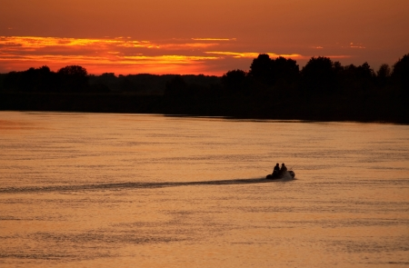Fishermen in a motor boat on the river photo