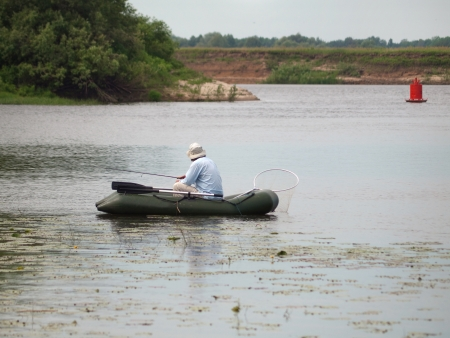 Fisherman in rubber boat on the river Stock Photo