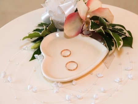 Wedding rings on the table with flowers