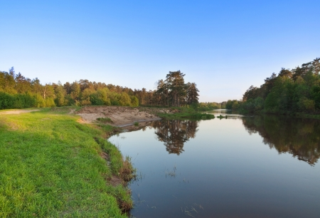 Forest landscape with clear blue sky and river Stock Photo