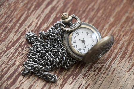 Closeup of metal vintage open pocket clock with chain on brown old wooden background. Stock Photo