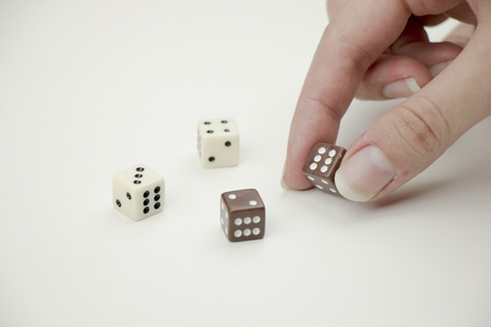 double game: Hand placing dice on white background.