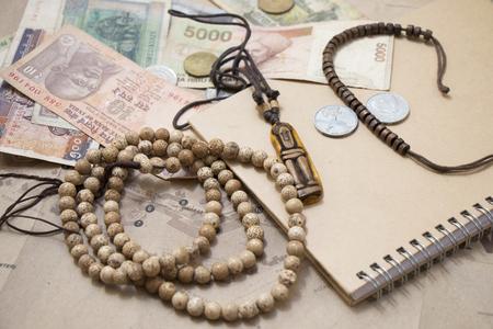 money packs: Traveling retro still life closeup with map, money, coins, buddhist mala bracelet, diary. Stock Photo