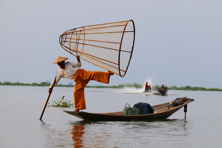 Traditional fisherman on a boat  in Inle lake, Myanmar. Stock Photo
