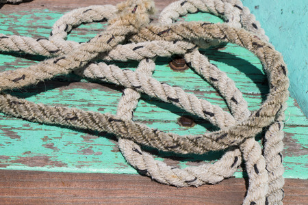 ship anchor: Closeup of rope on teal ship deck. Stock Photo