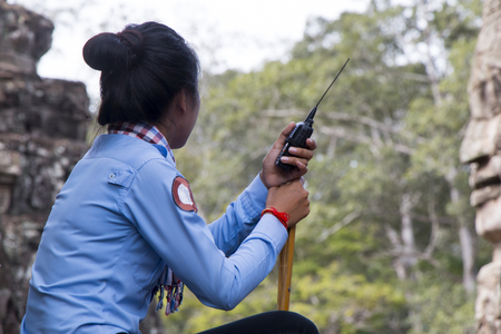 Female officer in blue uniform sitting with wireless trasnmitter in angkor temples area.
