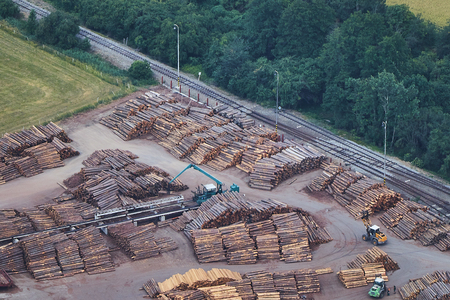 Aerial view of stacked lumber piles with heavy moving machinery and a railway track.
