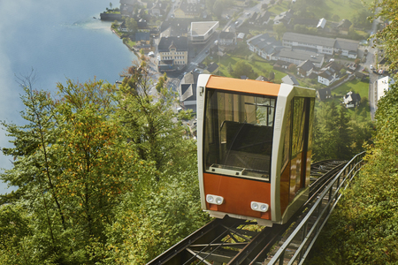 View of a Hallstatt cable car from the top station leading to a skywalk view in Austria with mist in the background. Stock Photo