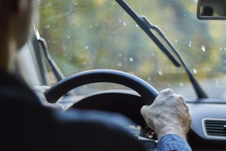 Back view of a man driving a car with moving windshield wipers during rain.