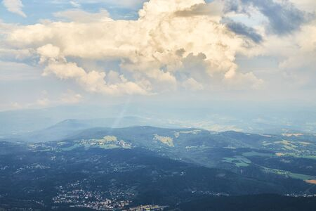 Aerial photo of bohemian landscape with fields, meadows, forests and villages and clouds in the sky