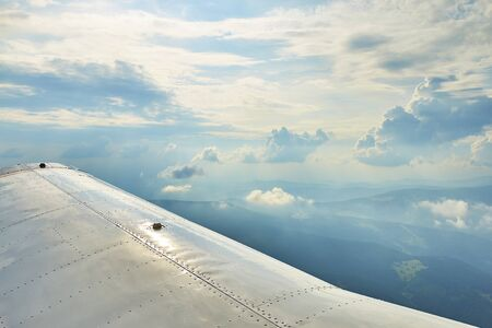 Aerial photo of a small plane wing and beautiful clouds in the sky and silhouettes of hills and meadows Standard-Bild