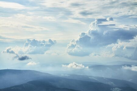 Aeial photo of beautiful clouds in blue sky with silhouettes of hills