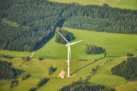 Aerial photo of beautiful landscape with meadows, forests and fields with a wind turbine