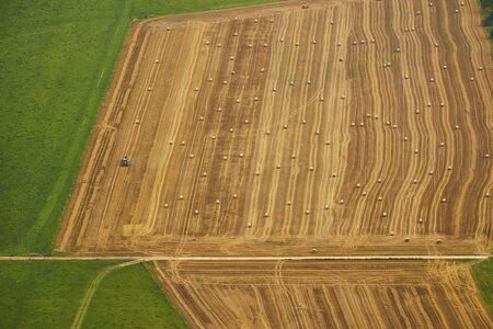 Aerial view of beautiful colorful field with harvesting machinery