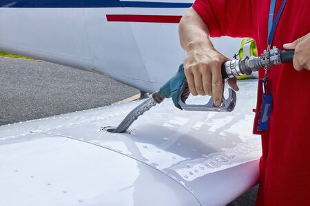 Close up of an aircraft worker fueling low-wing propeller driven airplane