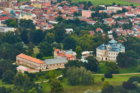 Chlumec nad Cidlinou, Czechia - 08/25/2019: Aerial photo of baroque castle Karlova Koruna surrounded by parks and trees and city in the background