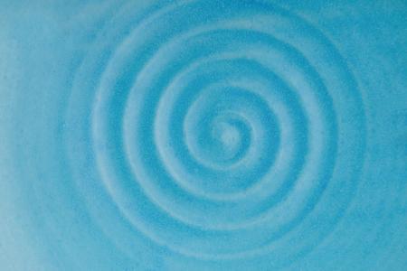Ceramic dish. Circular vibrations. Blue rippled water waves. Blue background
