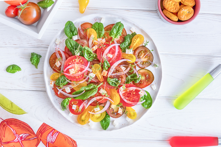 Fresh salad with colorful tomatoes, cheese, onion and spinach on a white background. Top view