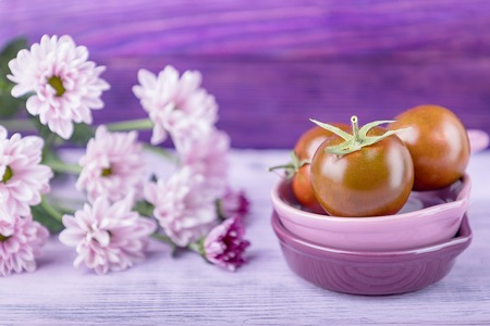Black prince tomatoes and delicate chrysanthemums on a wooden background. Free space