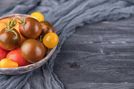 Ceramic bowl with various colorful tomatoes on dark wooden background. Free space