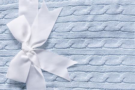 Baby knitted gray blue blanket. Cute gift for newborn baby with decorative white bow Standard-Bild