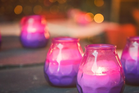 Bright burning purple and pink candles on the table