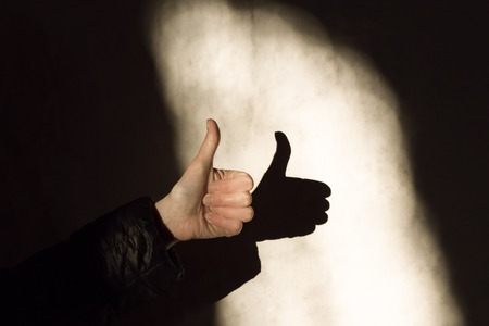 Woman hand thump up sign or like symbol and shadow on a wall