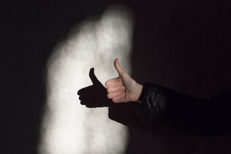 Woman hand thump up sign and shadow on a wall Stock Photo