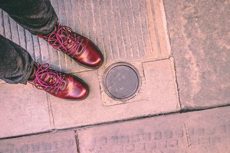 Feet selfie. Fashionable burgundy boots on the city pavement and electric metallic bollard under ground. Retractable bollard