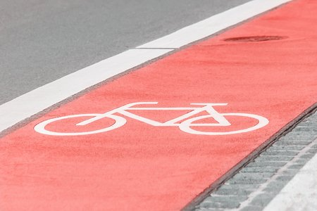 Bicycle path with a bicycle symbol on the asphalt road. Trendy coral color 2019 免版税图像