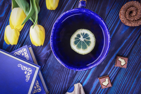 Tea with lemon, books and spring yellow tulips on a blue wooden background. Chocolate with a bunny figurine