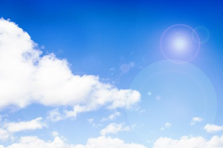 Fluffy white clouds on the blue color sky background. Sky with sun glare 版權商用圖片