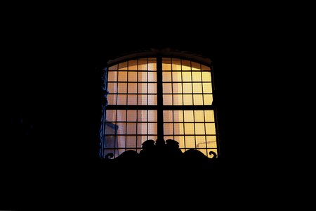 Window with yellow light on the black background. Copy space