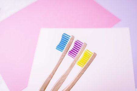 Yellow, violet and blue bamboo toothbrushes. Eco friendly concept. Minimal, colored geometric background. Copy space
