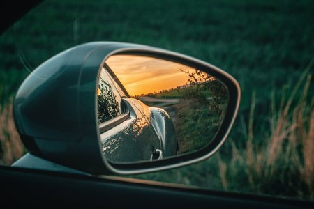 Beautiful sunset in the sideview mirror of the car. Green nature background