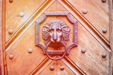 An ancient wooden door with door knocker in the shape of a lion. Orange toned