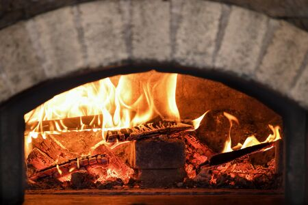 Traditional typical Italian oven for pizza and bread. Oven with bright fire. Copy space