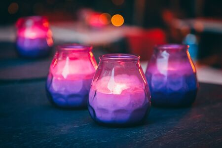 Hygge concept. Bright burning purple and pink candles on the dark table Фото со стока