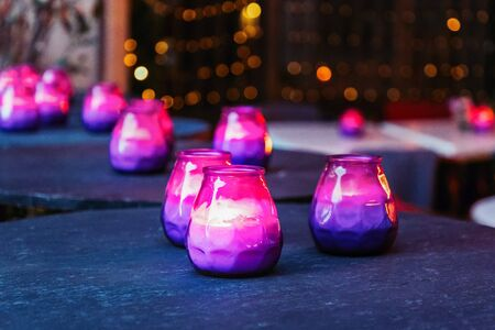 Hygge concept. Bright burning purple and pink candles on the dark table 版權商用圖片