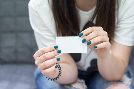 Female hands holding white empty business card. Manicure with turquoise blue nail polish Foto de archivo
