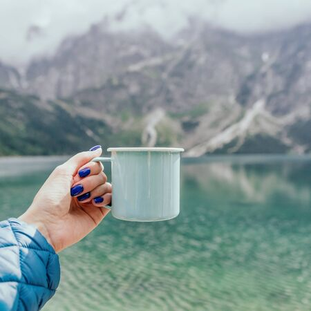 Female hand holding mint color enamel cup.Wonderful nature. Crystal clear lake and mountains. Tatra National park, Poland. Famous lake Morskie Oko or Sea Eye