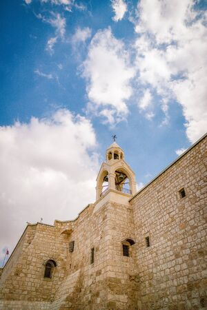 Church of the Nativity. Bell tower and beautiful cloudy sky. Details, fragment. Bethlehem, Palestine