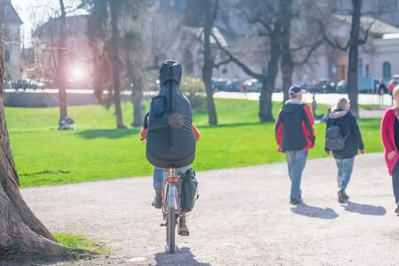 Person with a cello on a bicycle. Sun glare effect, spring mood