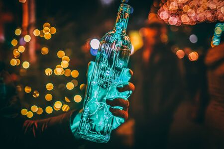 Magic Christmas. Green aqua color mint garland in the transparent bottle. Garland in the hand, toned photo, copy space