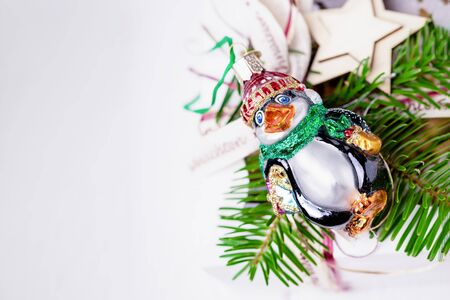 Merry Christmas and Happy New Year. Christmas tree branch and funny vintage penguin on a white background. Christmas decorations. Top view, copy space,
