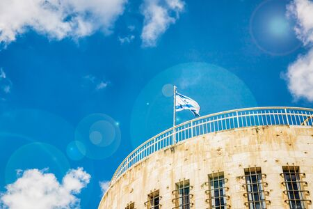 Jerusalem Historical City Hall Building, flag of Israel and blue sky. Fragment, details. Sky with sun glare Stock Photo