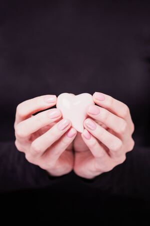 Beautiful female hands holding pale pink heart on the black background. Manicure with pink color nail polish. Copy space 版權商用圖片