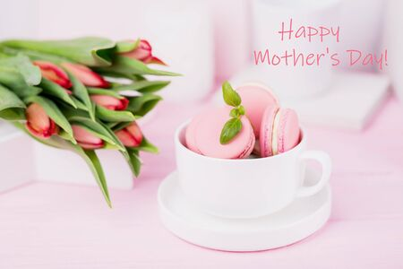 Happy Mothers Day concept. Inscription, text, words. Pink macarons and spring tulips on pink background Reklamní fotografie