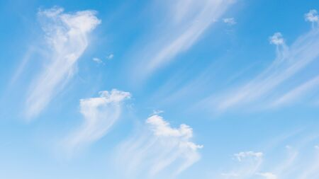 Beautiful white clouds on a light blue sky background. Clouds Like a brush strokes, 16 on 9 panoramic format 免版税图像