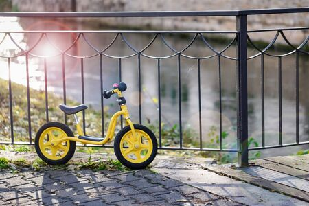 Children yellow bicycle parked in parking spot on the metal fence background. Sun glare effect